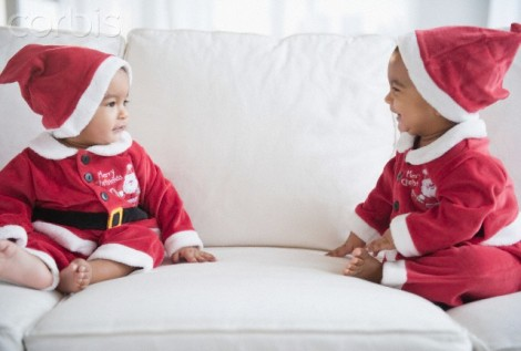 Twins on sofa dressed in Santa outfits